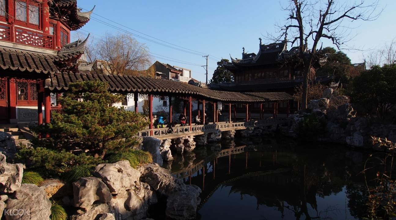 a bridge, a river, and a traditional Chinese architecture in the Yu Garden